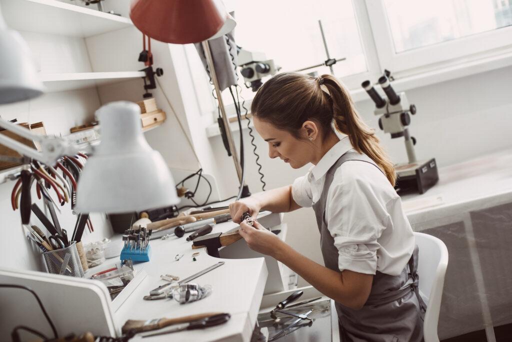 Junge Frau bearbeitet einen Ring in der Goldschmiede
