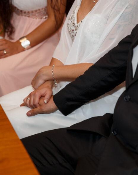 Das Brautpaar sitzt gemeinsam mit der Trauzeugin im Hintergrund bei der standesamtlichen Trauung.